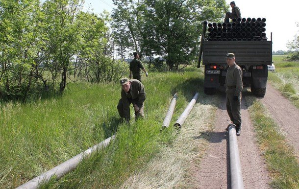 A picture taken near the eastern Crimea's village of Kirinichki on May 13, 2014, shows Soldiers of Russian Pipeline Troops unloading iron pipes from a trucks as they construct a water pipeline in the eastern Crimea.