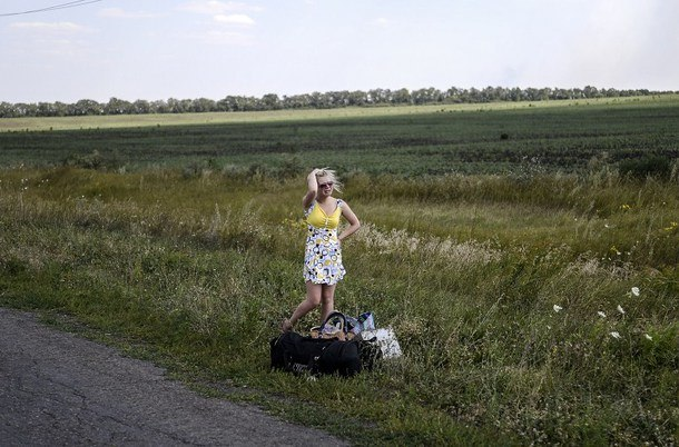 A Ukrainian girl cries as she stands on the road with her luggage after she left her home near the village of Grabove, some 80 kilometers east of Donetsk on Aug. 2.